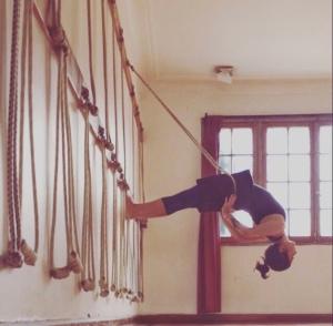 Dwi pada viparita dandasana en su versión con cuerdas o yoga kurunta.